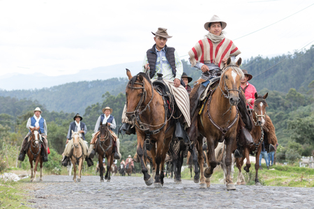 May 27, 2017 Sangolqui, Ecuador: a group of cowboys on horseback galloping on a country road in the Andes