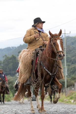 May 27, 2017 Sangolqui, Ecuador: cowboy on horse back wearing chaps riding to a rural rodeo in the Andes Editorial