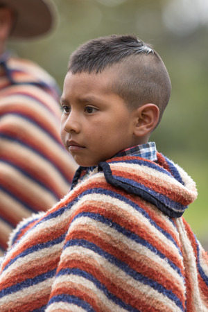 May 27, 2017 Sangolqui, Ecuador: young indigenous boy wearing traditional wool poncho closeup at a rural rodeo Redakční