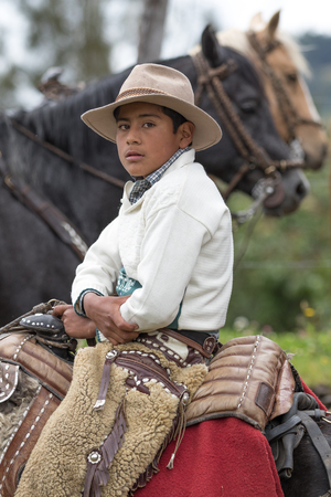 May 27, 2017 Sangolqui, Ecuador: young cowboy sitting in saddle wearing traditional furry chaps at a rural rodeo