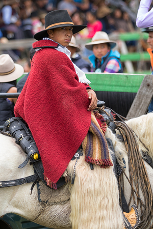 May 27, 2017 Sangolqui, Ecuador: young cowboy sitting in saddle wearing traditional wool poncho and furry chaps at a rural rodeo