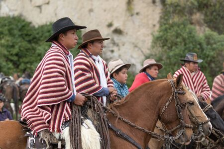 local 27: May 27, 2017 Sangolqui, Ecuador: local cowboys wearing traditional wool poncho watching the rural rodeo