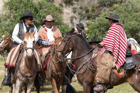 local 27: May 27, 2017 Sangolqui, Ecuador: closeup off local cowboys wearing traditional wool poncho on horse back during a rural rodeo