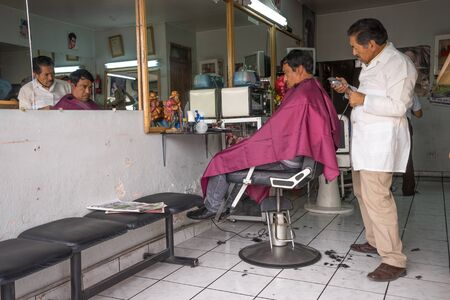 February 27, 2017 Ibarra, Ecuador: man getting a haircut in a local barber shop adjacent to the produce market