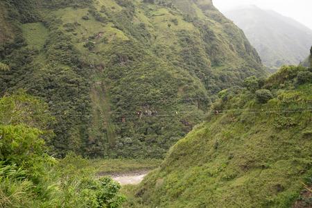Banos, Ecuador: tourists walking a suspended cable bridge above a deep canyon