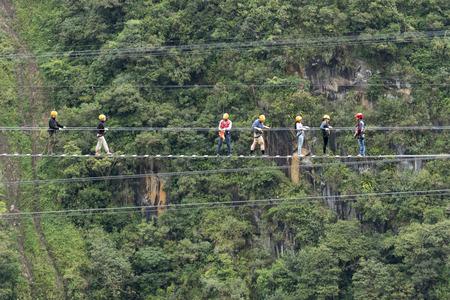 May 29, 2017 Banos, Ecuador: tourists walking a suspended cable bridge above a deep canyon