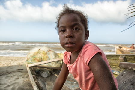 March 11, 2015 Sambo Creek, Honduras: a young garifuna girl part of the fishing community on the carribbean coast of the country sits on a dugout canoe Editorial