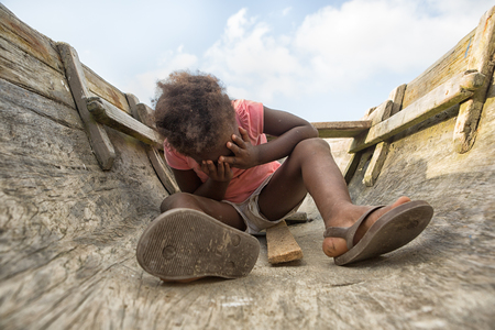 Sambo Creek, Honduras: a young garifuna girl sitting on the bottom of a dugout canoe with her palms over her face Stock Photo - 90103570