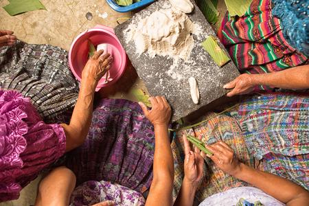 San Pedro la Laguna, Guatemala: Maya-vrouwen in traditionele kleding bereiden samen voedsel