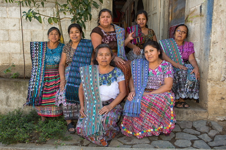 January 20, 2015 San Pedro la Laguna, Guatemala: a group of tzutujil mayan women  dressed in traditional clothing forming an artisan production shop