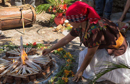January 31, 2015 San Pedro la Laguna, Guatemala: Mayan women lighting up fire started with candles at a  shamanic ritual in the Lake Atitlan area