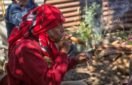 January 31, 2015 San Pedro la Laguna, Guatemala: tata Pedro Cruz one of the last authentic elderly Mayan shamans lighting a cigar during a ritual