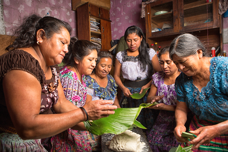 January 20, 2015 San Pedro la Laguna, Guatemala: Mayan women in traditional wear preparing food together