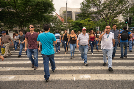 September 29, 2017 Medellin, Colombia: peoplewalk across a sidewalk on San Juan Avenue between Plaza Alpujarra and Plaza Cisnero