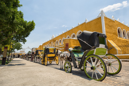 April 24, 2014 Izamal, Mexico: horse drawn carriages wating for tourists by the yellow convent of the colonia town Imagens - 87618540