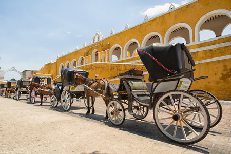 April 24, 2014 Izamal, Mexico: horse drawn carriages wating for tourists by the yellow convent of the colonia town
