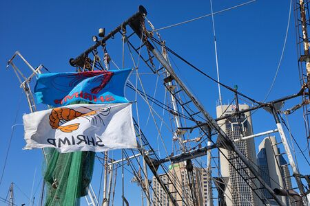 January 10, 2016 Corpus Christi, Texas, USA: flags fly on shrimping boats at the docks with downtown in the background Editorial