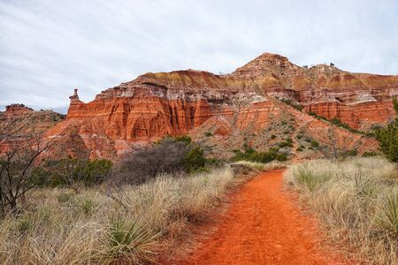hiking path leading towards eroded geological formation in Palo Duro canyon Texas Stock Photo