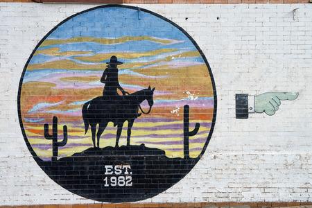 December 25, 2015 Fort Worth, Texas, USA: western themed graffiti on brick wall Editorial