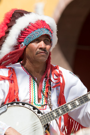 March 6, 2016, San Miguel de Allende, Mexico: indigenous man dressed in traditional costume playing the banjo at the Senior de la Conquista celebration