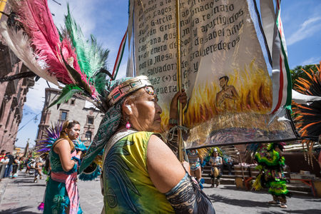 March 4,2016, San Miguel de Allende, Mexico: an  indigenous woman with traditional headdress holds up a religious banner at the Senior de la Conquista dance celebration