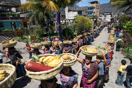 mayan tzutujil women lining up with fruit baskets on their head to enter the local church on easter holy week celebration Editorial