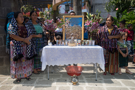 tzutujil maya women in traditional clothes standing by a praying station during holy week procession in san pedro la laguna guatemala