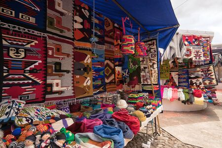 Otavalo, Ecuador- November 25, 2017: vendor stands with indigenous colourful textiles sold in the Saturday artisan market