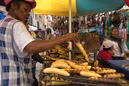 Otavalo, Ecuador-November 25, 2017: street vendor preparing baked bananas in the Saturday market