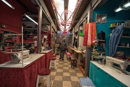 Ibarra, Ecuador - January 5, 2018: a man walks through the alteration shop section of the local market