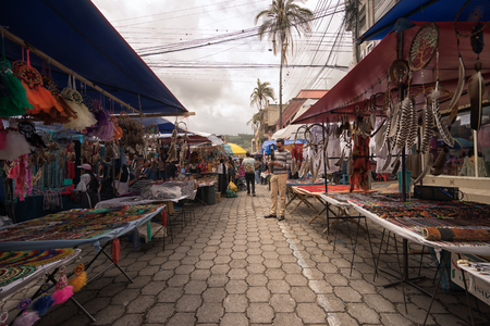 Otavalo, Ecuador-March 31,2018: a tourist stands between vendor stands set up on the street on market day Stock fotó - 98651370