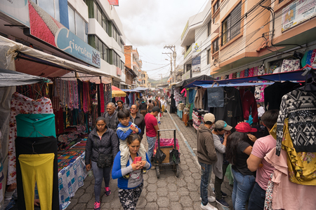 Otavalo, Ecuador-March 31,2018: people walk between the vendor stands set up on the street on market day Фото со стока - 98651373