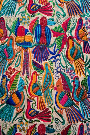 Otavalo, Ecuador- February 17, 2018: bird themed indigenous handcrafed textile closeup in the artisan market Фото со стока - 99763612