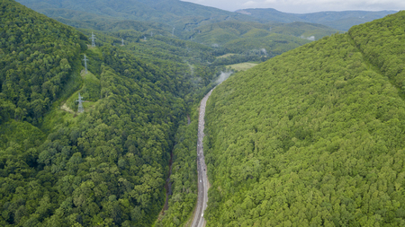 aerial stock footage of car driving along the winding mountain pass road through the forest in Sochi, Russia. People traveling, road trip on curvy road through beautiful countryside scenery. Stockfoto