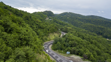 Panoramic view along the winding mountain pass road through the forest in Sochi, Russia. People traveling, road trip on curvy road through beautiful countryside scenery.