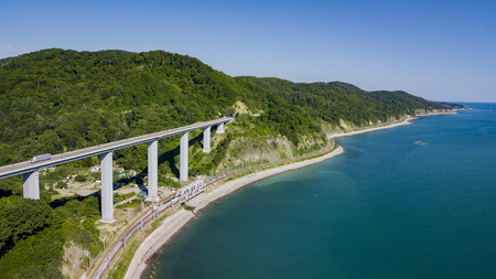 Aerial stock photo of car driving along the winding mountain pass road through the forest in Sochi, Russia. People traveling, road trip on curvy road through beautiful countryside scenery.