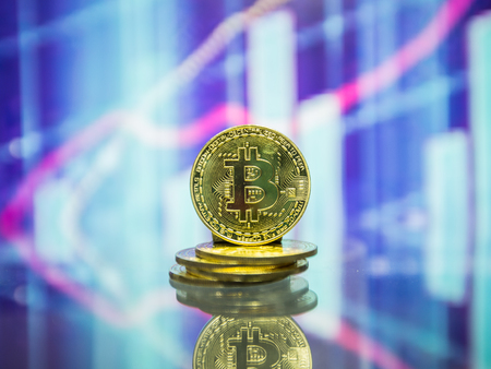 Golden bitcoin are stacked on a bright background of business graphs close-up. Bitcoin cryptocurrency. Stock Photo