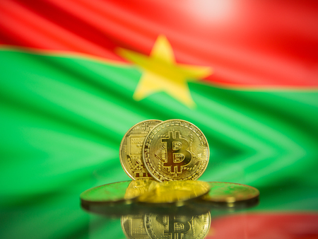 Bitcoin gold coin and defocused flag of Burkina Faso background. Virtual cryptocurrency concept.