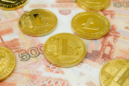 Litecoin coin cryptocurrency on 5000 Russian rubles banknotes close up. Golden LTC cryptocurrency.