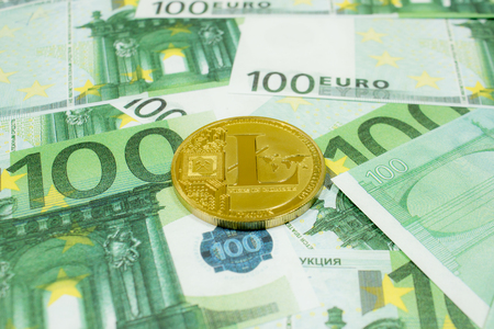 Litecoin coin cryptocurrency on 100 Euro banknotes close up. Golden LTC cryptocurrency.