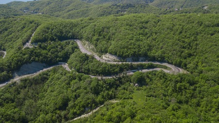 Aerial view of a curved winding road trough the mountains 免版税图像