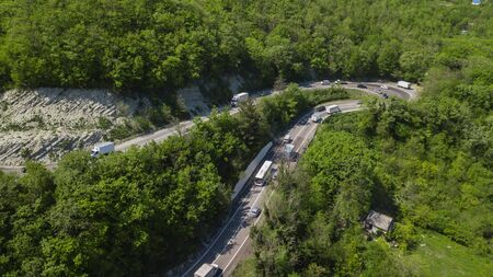Aerial view of a curved winding road trough the mountains Фото со стока