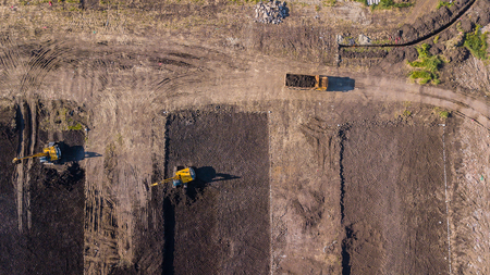 Aerial construction view of long arm excavator working on the field