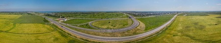 Aerial panoramic view of transportation highway overpass, ringway, roundabout, urban traffic Фото со стока