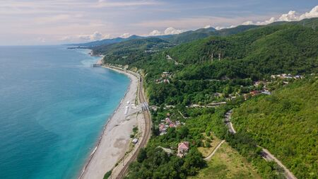 Birds Eye View - winding road from the high mountain pass in Sochi, Russia. Great road trip trough the dense woods. Standard-Bild