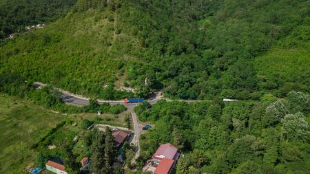 Birds Eye View - winding road from the high mountain pass in Sochi, Russia. Great road trip trough the dense woods.