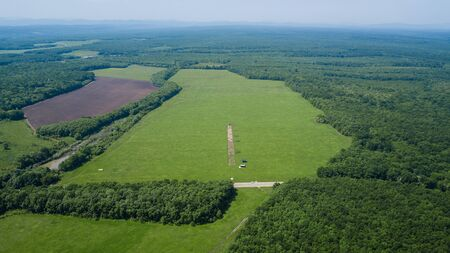 Aerial landscape nature - Dense green forest, green meadows, blue sky in southern Russia