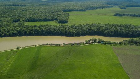 Aerial landscape nature - Dense green forest, green meadows, lake in southern Russia