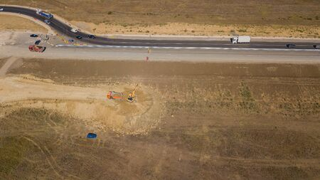 Aerial road constructions, machinery and mine equipment near road on sandy surface