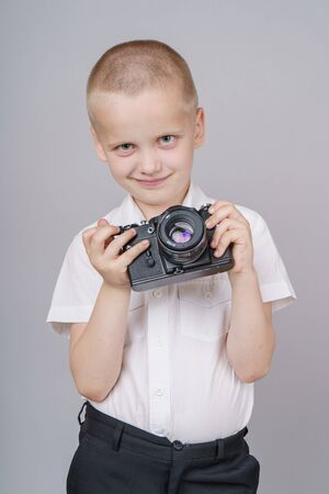 Child boy with retro compact camera, isolated on gray background.